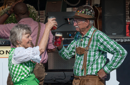 A salute to Oktoberfest is given with a couple in German costumes raising their beer glasses high
